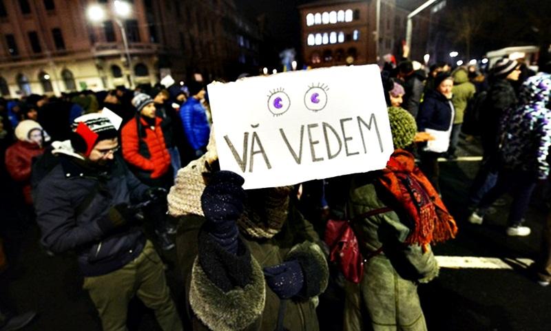 """O persoana tine in mana un carton cu mesajul """"VA VEDEM"""" in timpul protestului fata de intentia guvernului de a modifica prin Ordonanta de Urgenta mai multe prevederi ale codului penal,in Piata Universitatii din Capitala,  miercuri, 18 ianuarie 2017. ANDREEA ALEXANDRU / MEDIAFAX FOTO"""